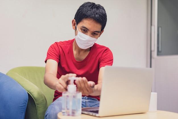 Covid-19, close up o homem usa uma máscara e lava gel de álcool nas mãos, contra o coronavírus em casa. trabalhe em casa, fique em casa, higienize as mãos
