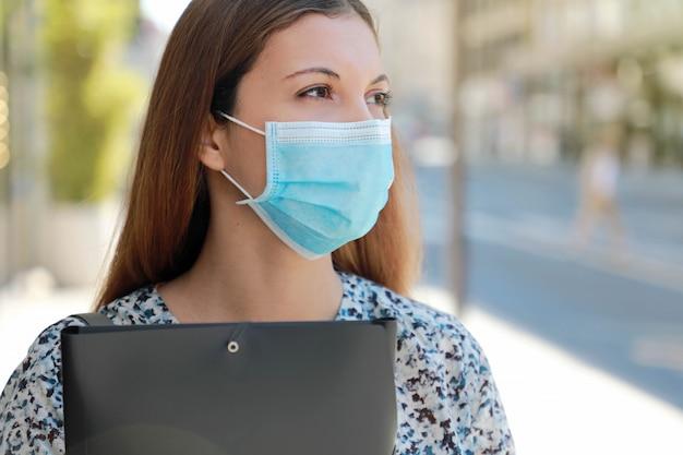 Covid-19 close up rapariga preocupada desempregada com máscara cirúrgica à procura de emprego caminhando na rua da cidade distribuindo curriculum vitae