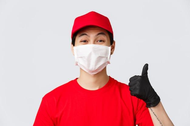 Covid-19, conceito de compras e entrega on-line com quarentena. correio asiático alegre em máscara médica e luvas de proteção, usar uniforme vermelho, mostrar o polegar para cima em aprovação, recomendar fazer pedidos seguros