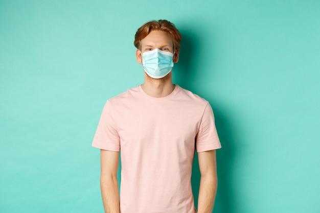 Covid-19, conceito de distanciamento social e quarentena. jovem ruivo, usando máscara médica de coronavírus em público, em pé sobre um fundo turquesa.