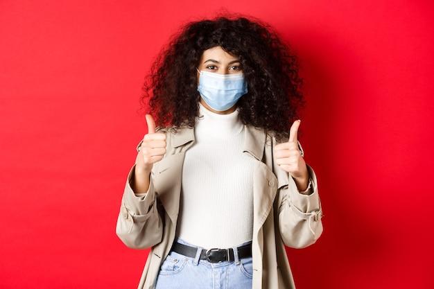 Covid-19, conceito de distanciamento social e quarentena. mulher elegante alegre vestindo gabardine e máscara médica para sair durante a pandemia, aparecendo o polegar.
