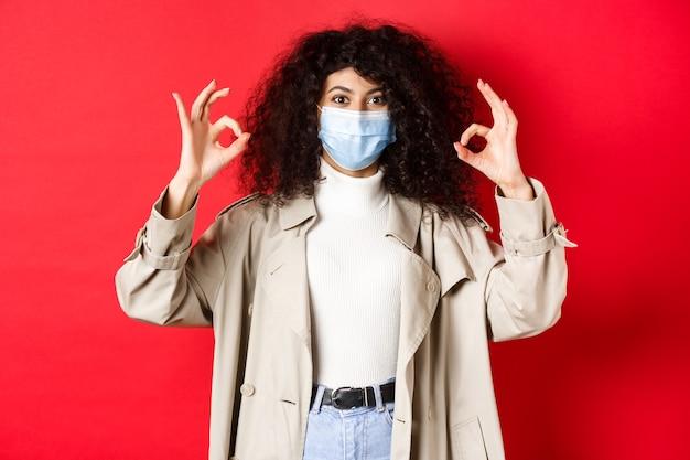 Covid-19, conceito de distanciamento social e quarentena. mulher elegante com cabelo encaracolado, usando máscara médica e gabardine, mostrando gestos bem, fundo vermelho.