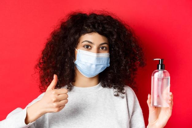 Covid-19, conceito de distanciamento social e quarentena. retrato de mulher com máscara facial de coronavírus, mostrando o frasco de desinfetante para as mãos e o polegar para cima, recomendando anti-séptico.