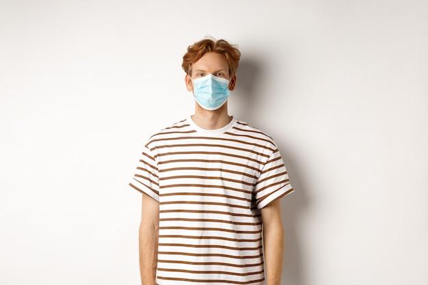 Covid-19, conceito de pandemia e distanciamento social. jovem com cabelo ruivo, usando máscara médica para evitar a captura de coronavírus, fundo branco.