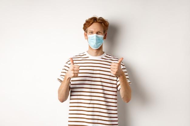 Covid-19, conceito de pandemia e distanciamento social. jovem com cabelo vermelho, usando máscara médica para evitar a captura de coronavírus, mostrando o polegar para cima, fundo branco.