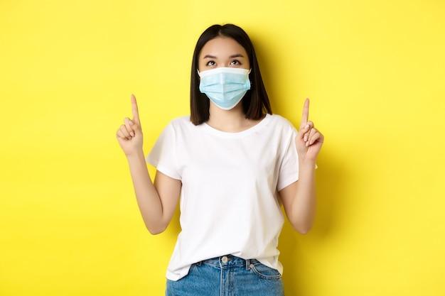 Covid-19, conceito de pandemia e distanciamento social. jovem mulher asiática com camiseta branca e máscara médica de coronavírus, olhando e apontando o dedo para cima, mostrando a oferta especial