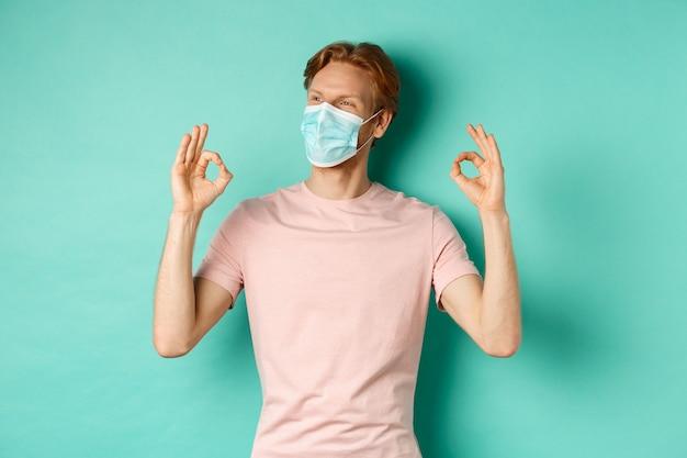 Covid-19, conceito de pandemia e estilo de vida. homem ruivo alegre na máscara médica, mostrando sinais de aprovação, gosto e elogio do produto, olhando para a esquerda no espaço da cópia.