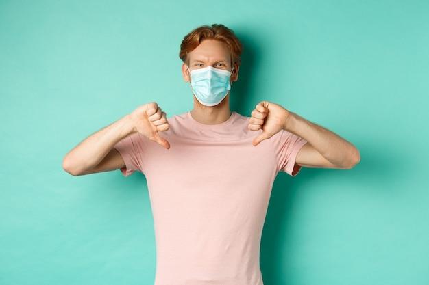 Covid-19, conceito de pandemia e estilo de vida. jovem com cabelo ruivo na máscara facial, mostrando os polegares para baixo, não gosta ou desaprova algo, em pé sobre um fundo turquesa.