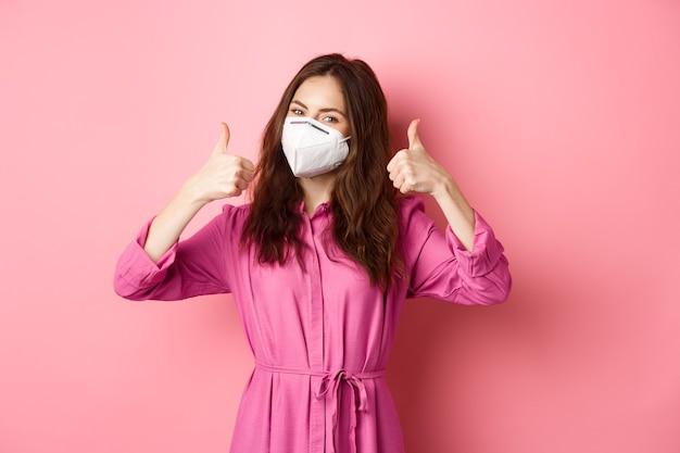 Covid-19, conceito de pandemia e estilo de vida. menina alegre mostra os polegares para cima, usa respirador médico como medida preventiva da parede corona, rosa.