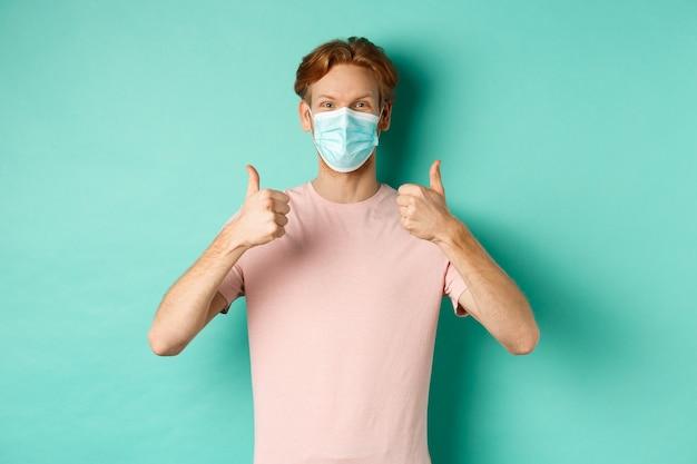 Covid-19, conceito de pandemia e estilo de vida. ruivo alegre com máscara médica mostrando os polegares em aprovação, gosto e elogio do produto, de pé sobre um fundo turquesa