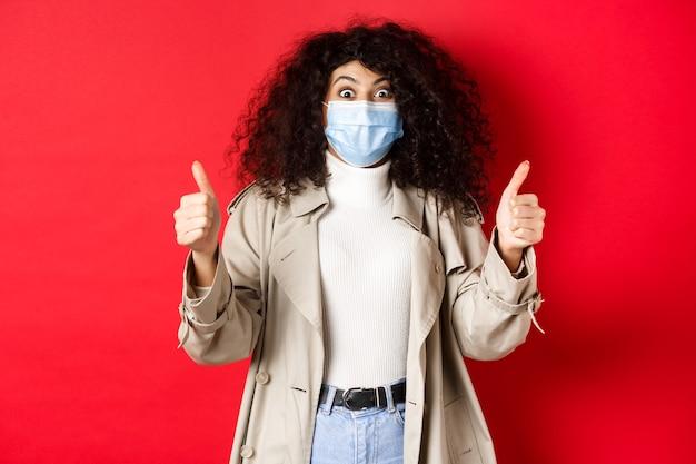 Covid-19, conceito de pandemia e quarentena. excitada garota com cabelo encaracolado, vestindo sobretudo e máscara médica, mostrando os polegares em aprovação, parede vermelha.