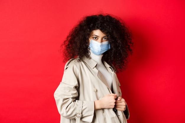 Covid-19, conceito de pandemia e quarentena. garota atrevida em gabardine e máscara médica, coloque gabardine para caminhada de primavera, parede vermelha.