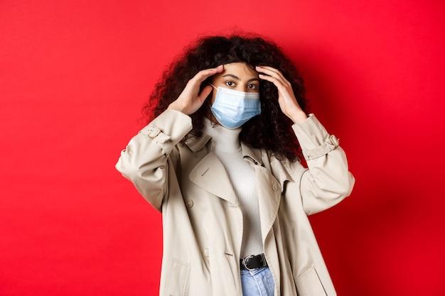 Covid-19, conceito de pandemia e quarentena. mulher jovem elegante com cabelo encaracolado, saindo com máscara médica e gabardine, consertando o corte de cabelo, sobre fundo vermelho.
