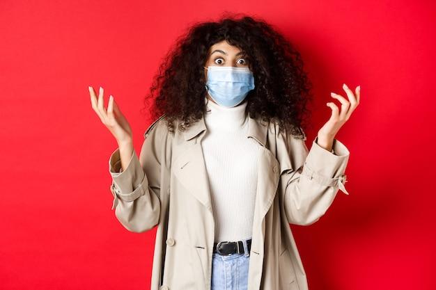 Covid-19, conceito de pandemia e quarentena. senhora chocada com cabelo encaracolado e máscara médica, levantando as mãos confusa, em pé na parede vermelha.