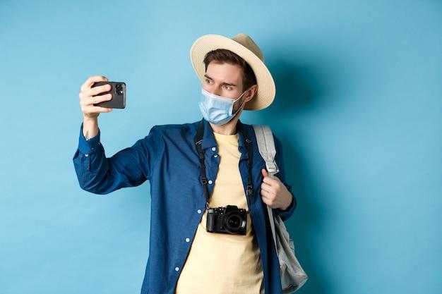 Covid-19, conceito de pandemia e viagens. turista masculino com chapéu de palha e máscara médica gravando vídeo no smartphone durante as férias, tirando fotos nas férias de verão, fundo azul.