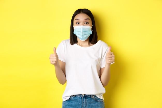 Covid-19, conceito de quarentena e distanciamento social. mulher asiática alegre na máscara médica e camiseta branca mostrando os polegares em aprovação, elogio bom negócio, fundo amarelo.