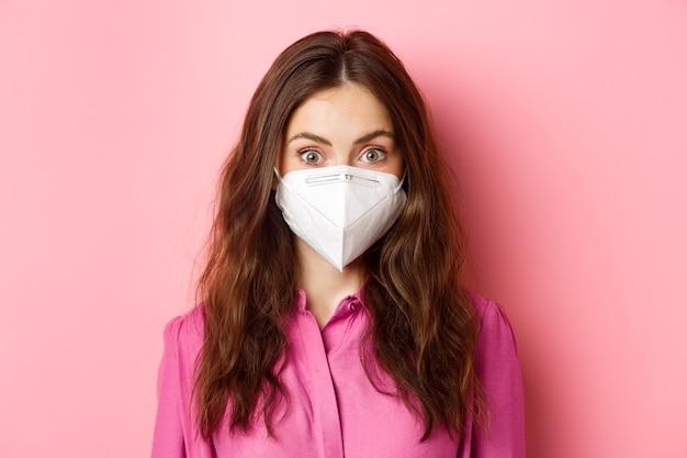 Covid-19, conceito de quarentena e distanciamento social. perto de uma jovem mulher elegante com um belo penteado, usando respirador médico de coronavírus, parede rosa.