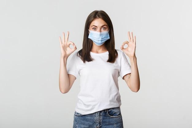 Covid-19, conceito de saúde e distanciamento social. menina bonita sorridente animada na máscara médica, mostrando o gesto bem satisfeito.