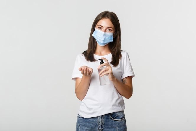 Covid-19, conceito de saúde e distanciamento social. mulher jovem e atraente morena na máscara médica, aplicando desinfetante para as mãos por lado, branco.