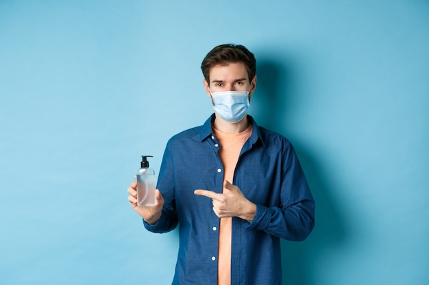 Covid-19, conceito de saúde e pandemia. homem sorridente com máscara médica mostrando desinfetante para as mãos, recomendando o frasco anti-séptico, de fundo azul.