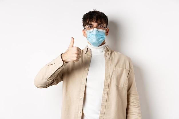 Covid-19, conceito de saúde e pessoas reais. cara satisfeito com máscara facial esterilizada e óculos, mostrando o polegar em aprovação, dá um feedback positivo, em pé na parede branca.
