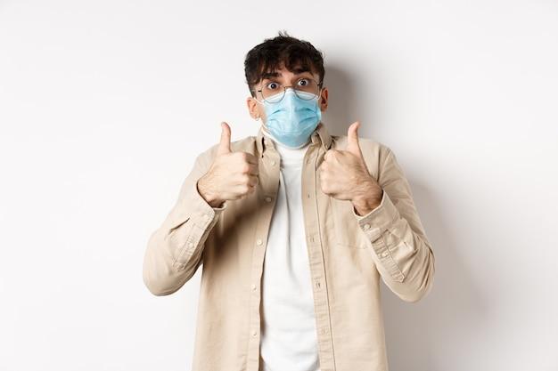 Covid-19, conceito de saúde e pessoas reais. homem alegre de óculos e máscara facial estéril, mostrando os polegares em aprovação, elogio e elogio do produto, de pé na parede branca.