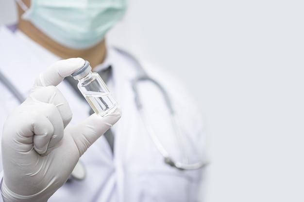 Covid 19 concept, doctor's hand em luvas azuis segura o frasco com a vacina em fundo azul