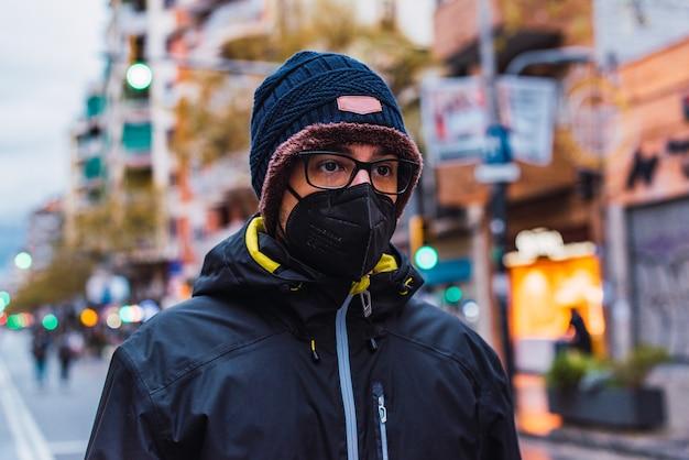Covid-19 coronavírus pandêmico jovem vestindo roupas de inverno em uma rua da cidade usando máscara facial