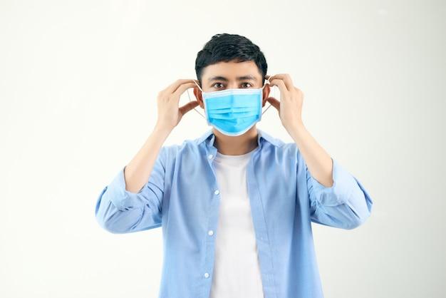 Covid-19 coronavirus retrato bonito jovem asiático usando máscara de proteção de covid 19 isolado na parede branca. pessoas do homem asiático. conceito covid-19.