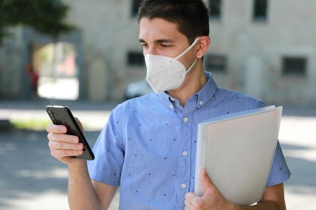 Covid-19 crise econômica global, homem desempregado com máscara, usando um telefone celular e entregando o curriculum vitae