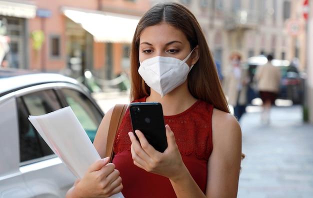 Covid-19 crise econômica global mulher desempregada com máscara, usando um telefone celular e entregando o curriculum vitae