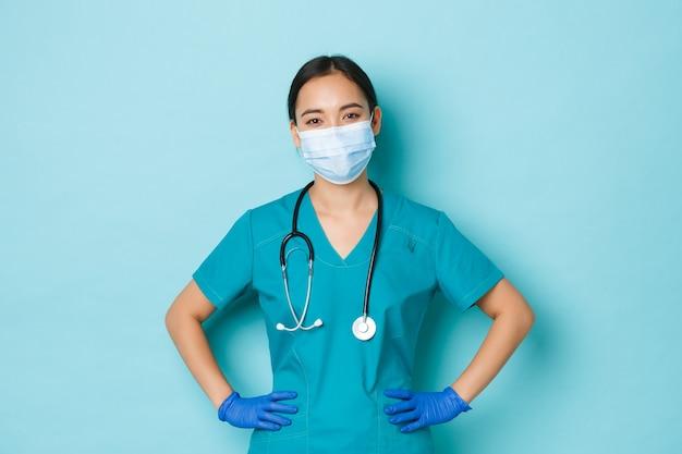 Covid-19, distanciamento social e conceito de pandemia de coronavírus. médica asiática sorridente alegre, enfermeira de uniforme e máscara médica, luvas, de pé determinado sobre uma parede azul clara