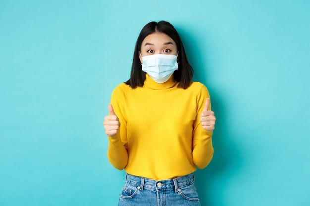 Covid-19, distanciamento social e conceito de pandemia. mulher asiática animada mostrando os polegares e parecendo impressionada, elogiando um bom negócio, usando máscara facial, fundo azul.
