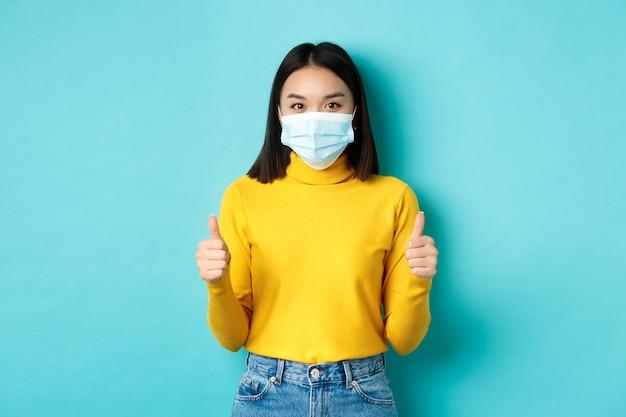 Covid-19, distanciamento social e conceito de pandemia. mulher asiática de apoio recomenda promoção, usando máscara médica e mostrando os polegares para cima, em pé sobre um fundo azul.