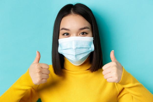 Covid-19, distanciamento social e conceito de pandemia. perto de uma jovem mulher asiática em máscara médica aparecendo os polegares, dê aprovação, elogie a boa oferta, em pé sobre fundo azul.