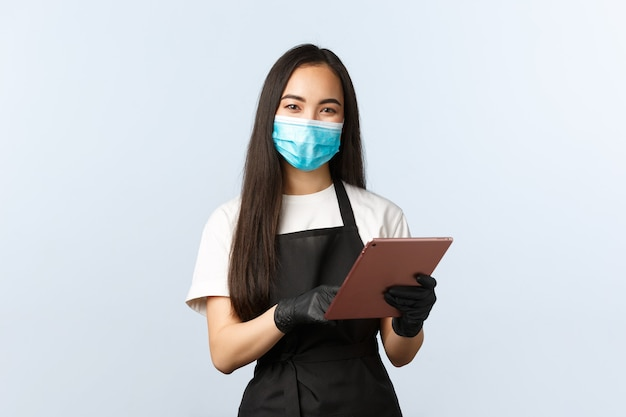 Covid-19, distanciamento social, pequena cafeteria e conceito de prevenção de vírus. sorridente e fofa barista asiática, funcionárias do café anotando o pedido com tablet digital, usam máscara médica e luvas