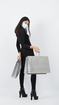 Covid 19 e o conceito de compras. mulher asiática usando máscara facial espera a sacola de compras. menina e sacola de papel representam compras durante a crise do coronavírus ou surto de covid19. comprador e máscara de vírus.