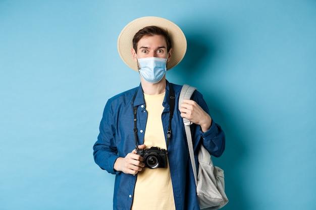 Covid-19 e o conceito de viagem. turista de cara jovem com máscara médica e chapéu de verão viajar para o exterior durante a pandemia de coronavírus, tirando fotos de férias, fundo azul.