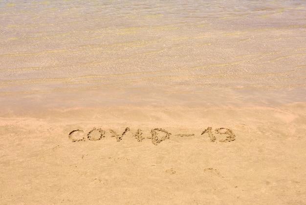 Covid-19 escrito na areia sendo levada pela maré enchente em uma praia tropical em creta, grécia.