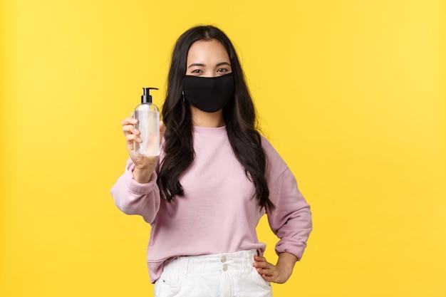 Covid-19, estilo de vida de distanciamento social, impede o conceito de propagação de vírus. menina asiática alegre na máscara facial, sempre usando desinfetante para as mãos durante a pandemia de coronavírus, recomenda um produto de higiene.