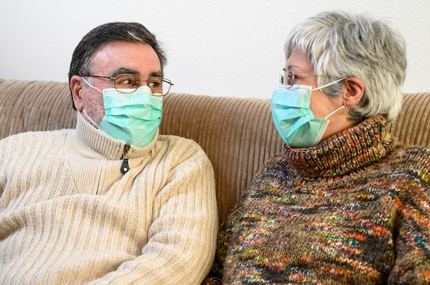 Covid-19, fique em casa estilo de vida. casal de idosos alegres com máscaras protetoras, sentado em um sofá, rindo e olhando um ao outro, sendo positivo durante a quarentena em casa.