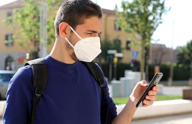 Covid-19 jovem vestindo máscara ffp2 usando um telefone inteligente na rua