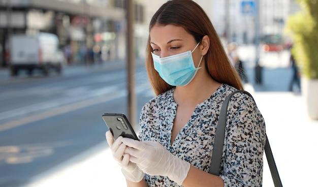Covid-19 mulher usando máscara cirúrgica e luvas protetoras usando aplicativo para telefone móvel na rua da cidade