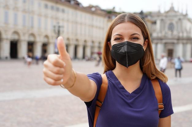Covid-19 mulher viajante otimista usando máscara protetora preta kn95 ffp2 mostrando o polegar para cima na praça da cidade