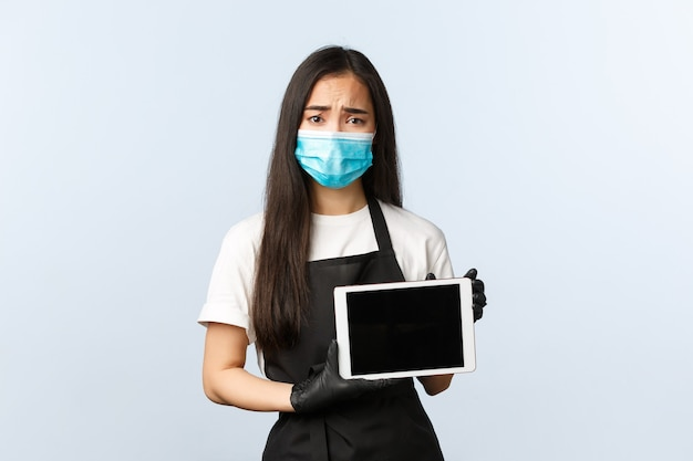 Covid-19 pandemia, distanciamento social, pequenas empresas e conceito de prevenção de vírus. garçonete asiática triste e triste, equipe de café usando máscara médica e luvas, carrancuda e triste e exibindo tela de tablet digital