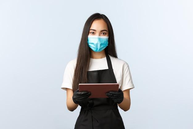 Covid-19, pedidos online, pequena loja de café e conceito de prevenção de vírus. barista asiática de aparência amigável pronta para anotar seu pedido, usar máscara médica e luvas e segurar um tablet digital