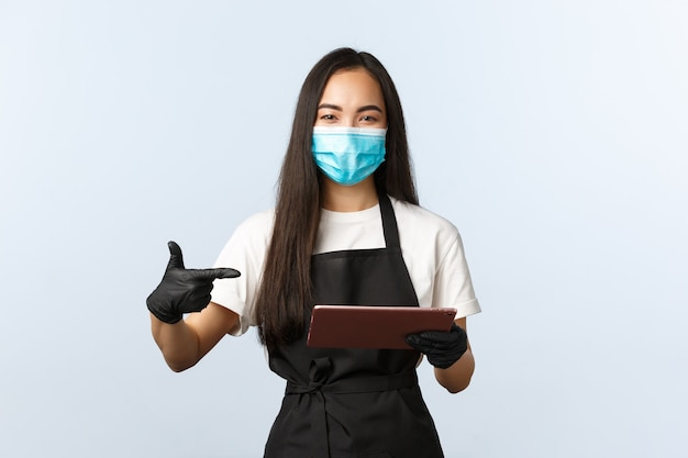 Covid-19, pedidos online, pequena loja de café e conceito de prevenção de vírus. barista asiática sorridente, garçonete com máscara médica e luvas apontando para o tablet digital, anotando o pedido do consumidor.