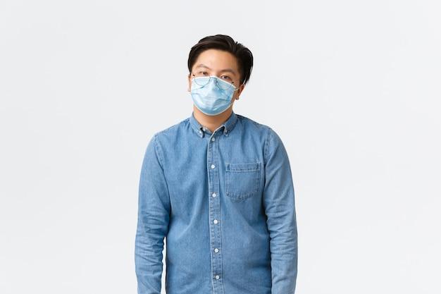 Covid-19, prevenção de vírus e distanciamento social no conceito de local de trabalho. trabalhador do sexo masculino asiático sobrecarregado e cansado, parecendo relutante, usando máscara médica, sentindo-se entediado, fundo branco de pé