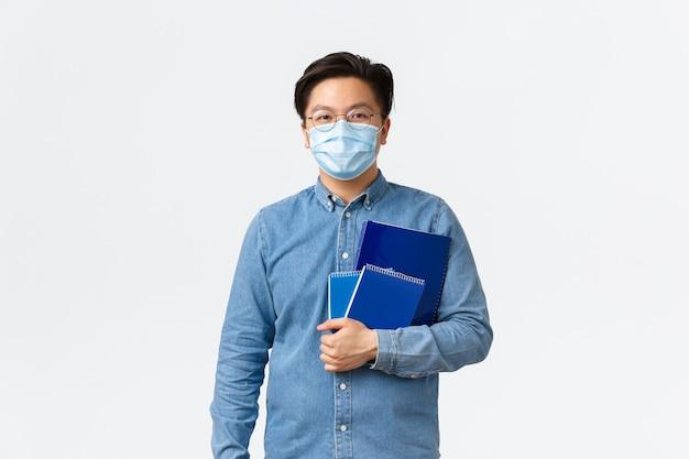 Covid-19, prevenção de vírus e distanciamento social no conceito de universidade. bonito e jovem tutor asiático, professor ou aluno com máscara médica carregam cadernos para aula, fundo branco.