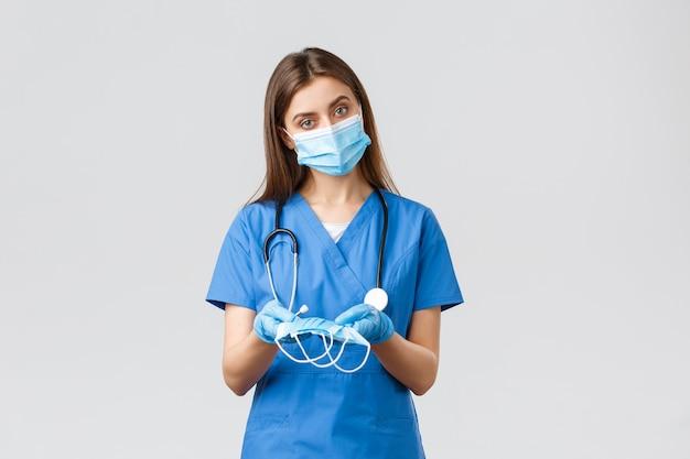 Covid-19, prevenção de vírus, saúde, profissionais de saúde e conceito de quarentena. enfermeira atraente com uniforme azul e equipamento de proteção individual, dando máscaras médicas ao paciente